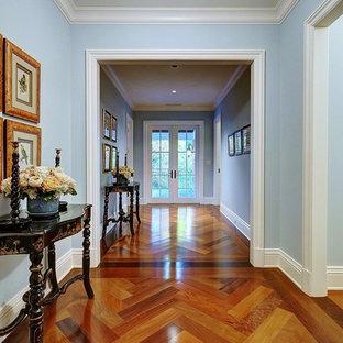 Exemple d'un couloir chic avec un mur bleu et un sol en bois brun.