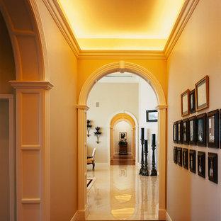 Пример оригинального дизайна: огромный коридор в средиземноморском стиле с бежевыми стенами, темным паркетным полом, коричневым полом и сводчатым потолком