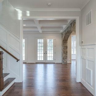 Foto på en vintage hall, med vita väggar, mellanmörkt trägolv och brunt golv