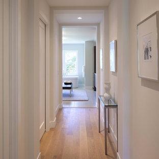 Idéer för en modern hall, med vita väggar och mellanmörkt trägolv
