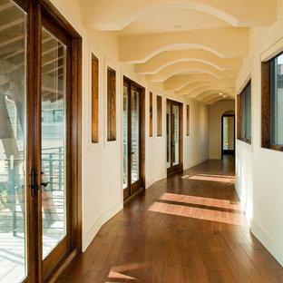 Réalisation d'un couloir méditerranéen avec un mur beige, un sol en bois brun et un sol orange.
