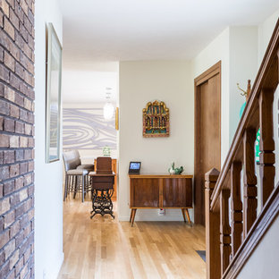 Photo of a mid-sized midcentury hallway in Omaha with white walls, light hardwood floors and white floor.
