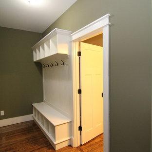 Réalisation d'un petit couloir tradition avec un sol en bois foncé et un mur vert.