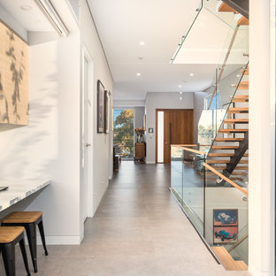 Photo of a mid-sized contemporary hallway in Sydney with white walls, beige floor and porcelain floors.
