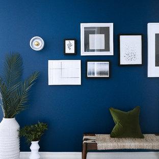 Réalisation d'un couloir design de taille moyenne avec un mur bleu, un sol en bois clair et un sol beige.