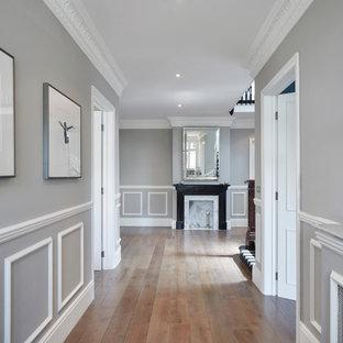 Esempio di un grande ingresso o corridoio tradizionale con pareti grigie, pavimento in legno massello medio, pavimento marrone e pannellatura