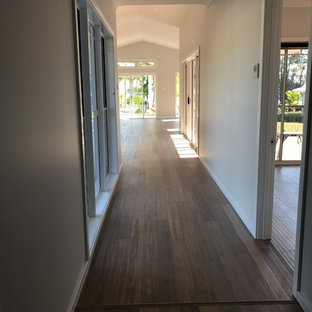 Design ideas for a mid-sized beach style hallway in Central Coast with grey walls, bamboo floors and brown floor.