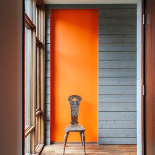 Cette image montre un couloir design avec un mur orange et un sol en bois brun.