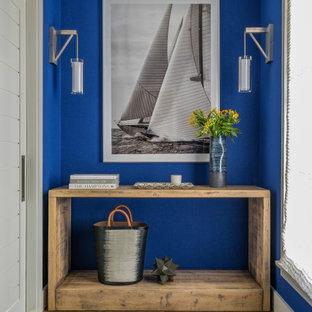 Idee per un ingresso o corridoio stile marinaro con pareti blu, pavimento in legno massello medio e pavimento marrone