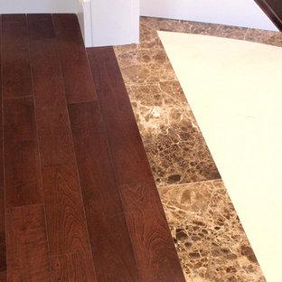 Example of a large minimalist dark wood floor and brown floor hallway design in Vancouver with beige walls