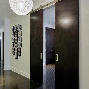 オタワのコンテンポラリースタイルのおしゃれな廊下 (ベージュの壁、濃色無垢フローリング、黒い床) の写真