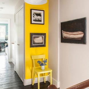 Bild på en mellanstor eklektisk hall, med gula väggar och mörkt trägolv