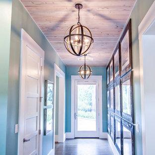 Réalisation d'un grand couloir ethnique avec un mur bleu et un sol en bois foncé.