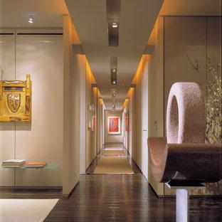 Ejemplo de recibidores y pasillos actuales con paredes beige, suelo de madera oscura y suelo marrón