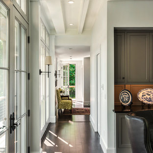 This is an example of a beach style hallway in Portland Maine with white walls and dark hardwood floors.