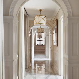 Cette photo montre un grand couloir chic avec un mur beige, un sol beige et boiseries.