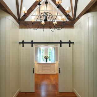 Klassisk inredning av en hall, med mellanmörkt trägolv, beige väggar och brunt golv