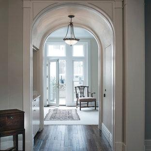 Idéer för att renovera en mellanstor vintage hall, med beige väggar, mörkt trägolv och svart golv