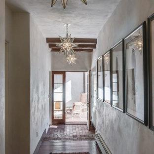 На фото: коридор среднего размера в стиле фьюжн с белыми стенами и кирпичным полом