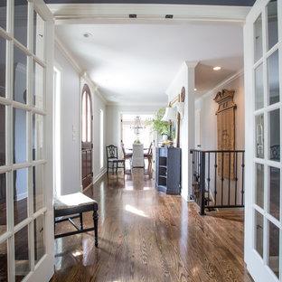 他の地域の広いトラディショナルスタイルのおしゃれな廊下 (白い壁、無垢フローリング、茶色い床) の写真