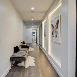 ロサンゼルスの広いコンテンポラリースタイルのおしゃれな廊下 (白い壁、無垢フローリング、黒い床) の写真