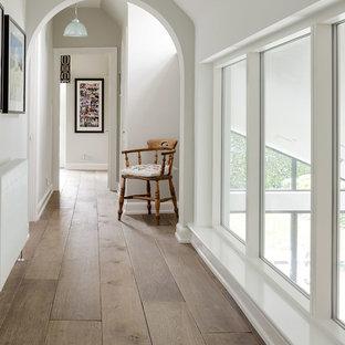 Ispirazione per un ingresso o corridoio classico con pareti bianche e pavimento in legno massello medio