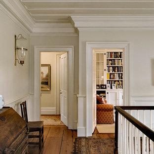 Idéer för en klassisk hall, med vita väggar, mellanmörkt trägolv och brunt golv