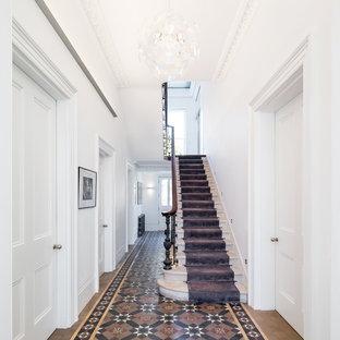 ロンドンの中くらいのトラディショナルスタイルのおしゃれな廊下 (白い壁、セラミックタイルの床、マルチカラーの床) の写真