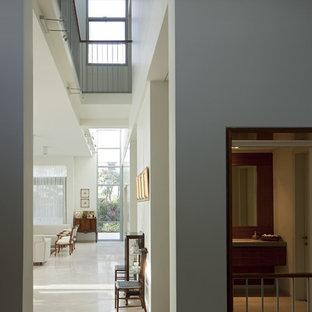 Свежая идея для дизайна: огромный коридор в стиле модернизм с белыми стенами и полом из известняка - отличное фото интерьера