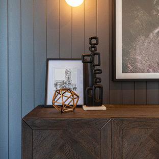 Cette photo montre un couloir avec un mur gris, un sol en bois clair, un sol beige et du lambris.