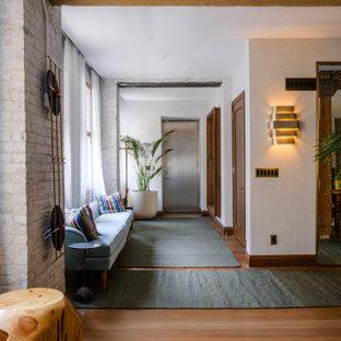 Aménagement d'un grand couloir contemporain avec un mur blanc, un sol marron et un plafond en poutres apparentes.