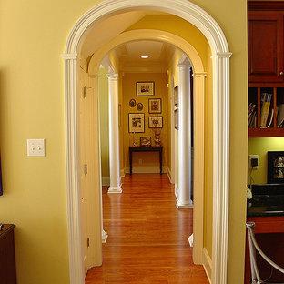 Exempel på en liten klassisk hall, med gula väggar, mellanmörkt trägolv och brunt golv