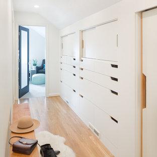 Exemple d'un petit couloir scandinave avec un mur blanc et un sol en bois clair.
