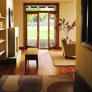 Inspiration för mellanstora moderna hallar, med gula väggar, mörkt trägolv och brunt golv