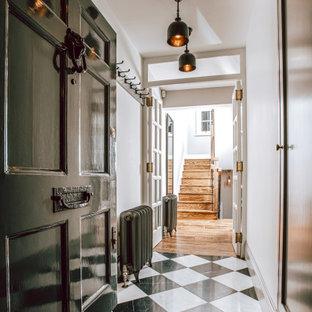 Réalisation d'un grand couloir design avec un mur gris, un sol en terrazzo et un sol noir.