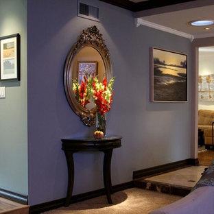 Exemple d'un couloir chic de taille moyenne avec un mur violet, un sol en travertin et un sol beige.