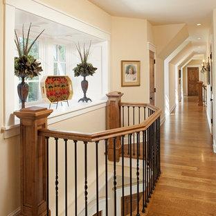 Inspiration pour un couloir traditionnel avec un mur beige, un sol en bois brun et un sol jaune.