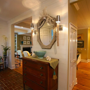 Mid-sized beach style hallway in Jacksonville with white walls, brick floors and red floor.