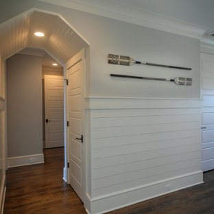 Inspiration for a mid-sized beach style hallway in Charleston with white walls, dark hardwood floors and brown floor.