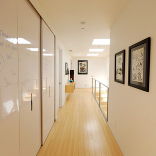Example of a minimalist light wood floor and yellow floor hallway design in Los Angeles with white walls