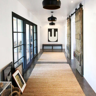 Cette photo montre un couloir nature avec un mur blanc, béton au sol et un sol marron.