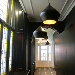 Inspiration for a huge contemporary ceramic floor and black floor hallway remodel in London with black walls
