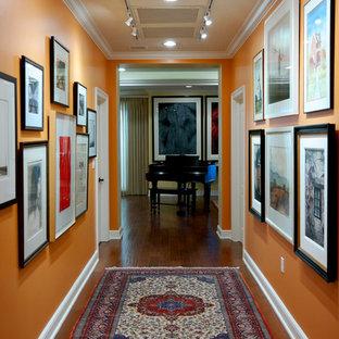 Exemple d'un couloir chic de taille moyenne avec un mur orange, un sol en bois foncé et un sol marron.