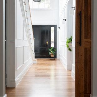 Exempel på en stor klassisk hall, med vita väggar och ljust trägolv