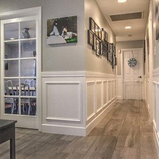 Cette image montre un grand couloir traditionnel avec un mur gris et un sol en carrelage de porcelaine.