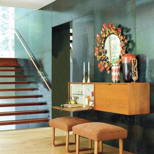 Trendy light wood floor and beige floor hallway photo in New York with green walls