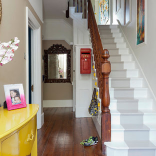 Cette photo montre un couloir éclectique de taille moyenne avec un mur beige, sol en stratifié et un sol marron.