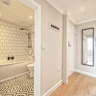 Пример оригинального дизайна: маленький коридор в современном стиле с серыми стенами, полом из ламината и коричневым полом