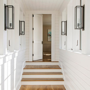 This is an example of a beach style hallway in Charleston with white walls, medium hardwood floors, timber and planked wall panelling.