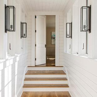 Maritimer Flur mit weißer Wandfarbe, braunem Holzboden, Holzdielendecke und Holzdielenwänden in Charleston